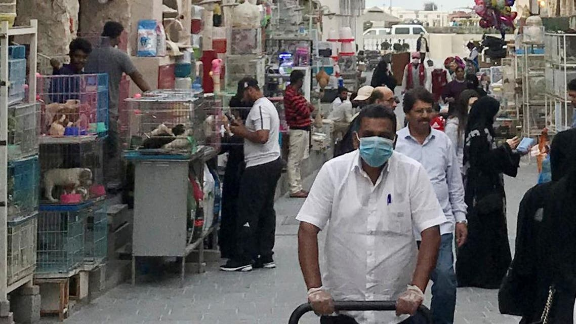 A man wears a protective face mask, following the outbreak of coronavirus, as he pushes a cart in Souq Waqif in Doha, Qatar, March 12, 2020. (Reuters)