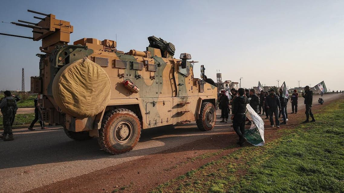 Syrians in protest stand before a Turkish military MRAP (Mine-Resistant Ambush Protected) vehicle as they attempt to block traffic on the M4 highway, which links the northern Syrian provinces of Aleppo and Latakia. (AFP)