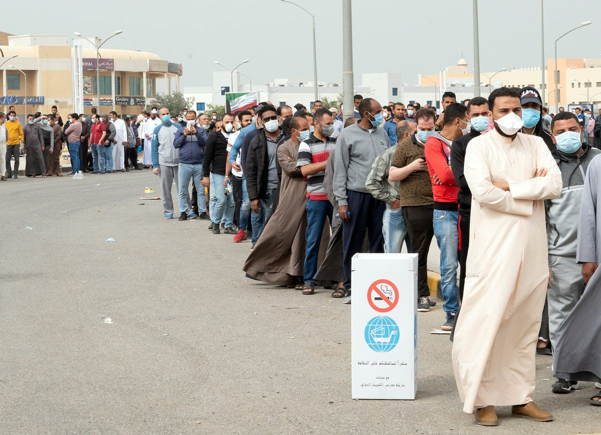 Expatriates wait in line to be tested at a makeshift center, following the outbreak of coronavirus, in Mishref, Kuwait March 14, 2020. (Reuters)