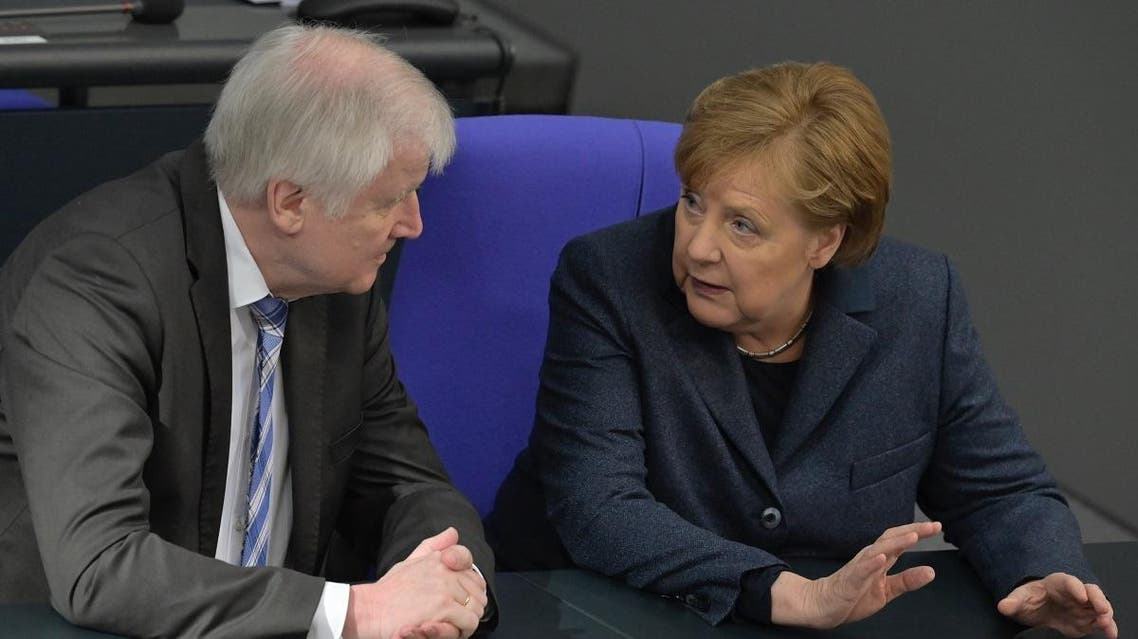 German Interior Minister Horst Seehofer chats with Chancellor Angela Merkel during a session of the German lower house of parliament Bundestag in Berlin on March 4, 2020. (AFP)