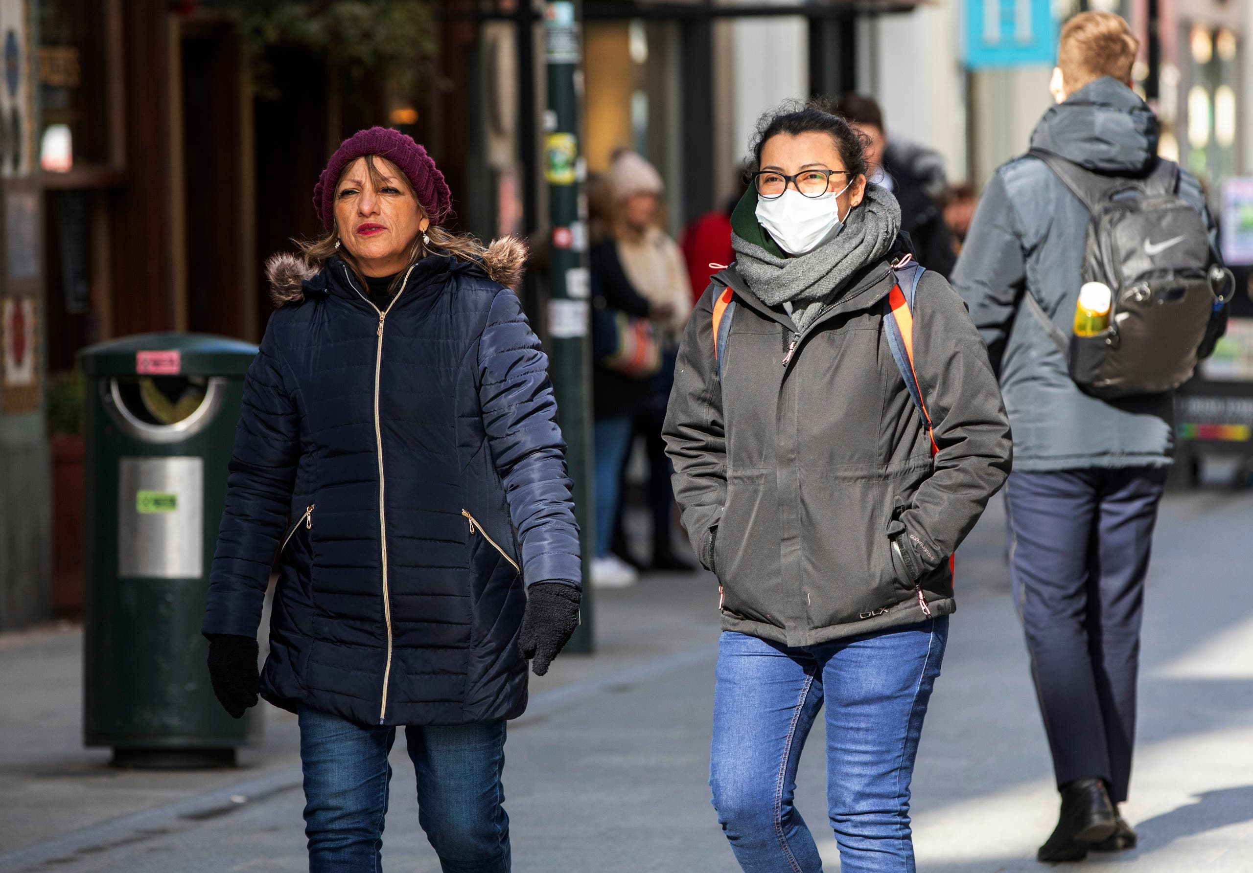 A woman wears a surgical mask while shopping in the Grafton shopping area of in Dublin on March 12, 2020. (AP)