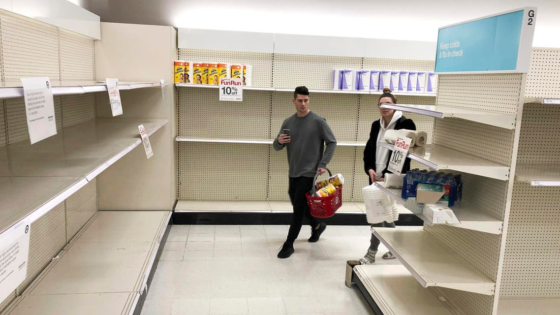 Shoppers walk through nearly empty shelves that usually hold toilet paper and paper towels, on Saturday, March 14, 2020, in a Target store in Olympia, Washington. (AP)