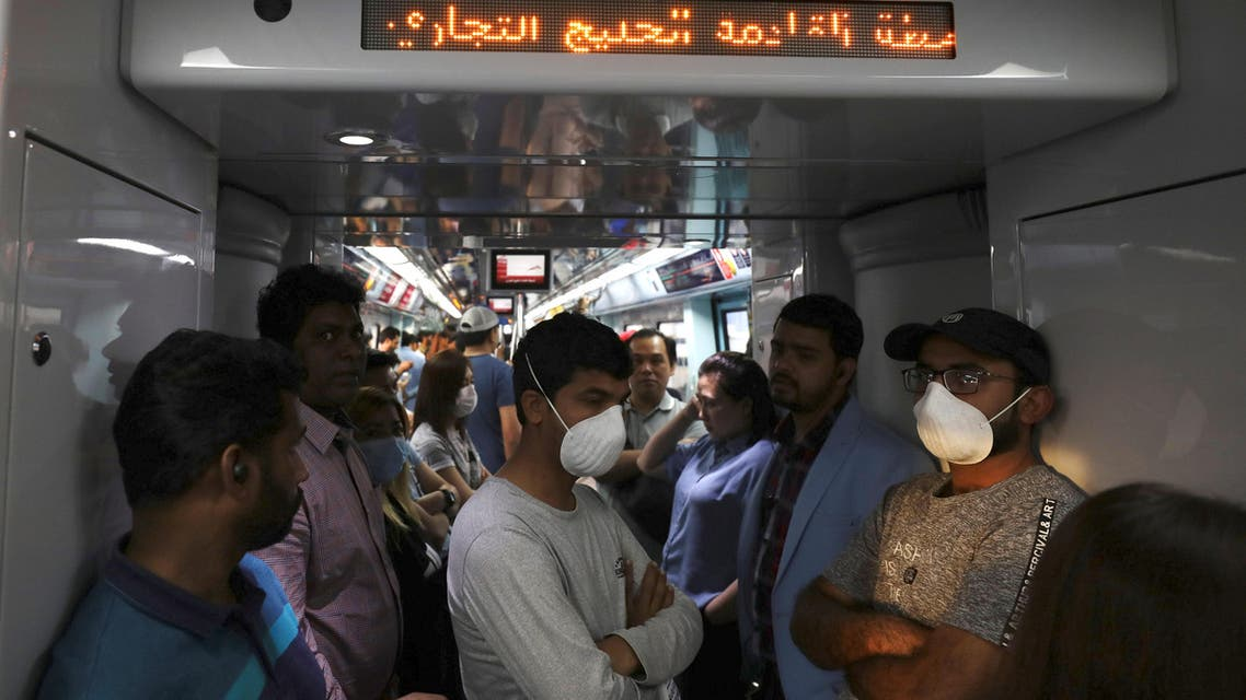 Commuters wear protective masks, following the outbreak of the coronavirus, on the metro in Dubai, United Arab Emirates, March 12, 2020. (Reuters)