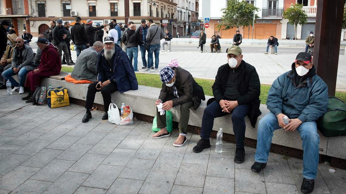 Moroccan nationals residing in countries such as France and Italy sit on a bench in the city of Algeciras on March 15, 2020, after being blocked from travel due to the lockdown measures. (AFP)
