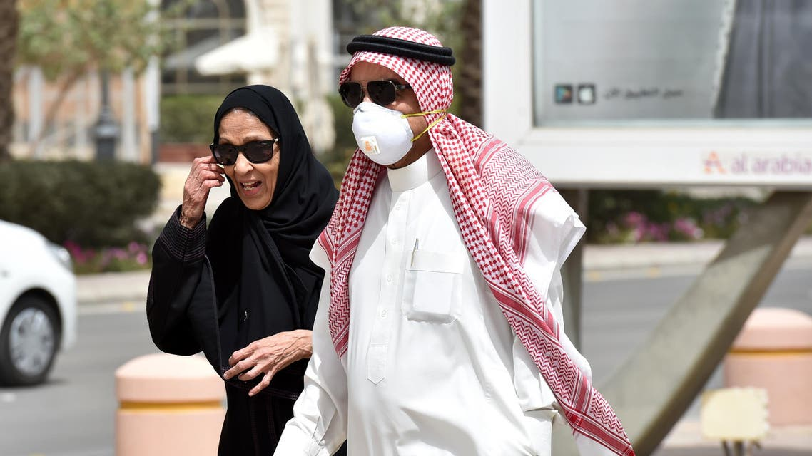 A Saudi man, wearing a protective mask as a precaution against coronavirus, walks with his wife along Tahlia street in the center of the capital Riyadh on March 15, 2020. (AFP)