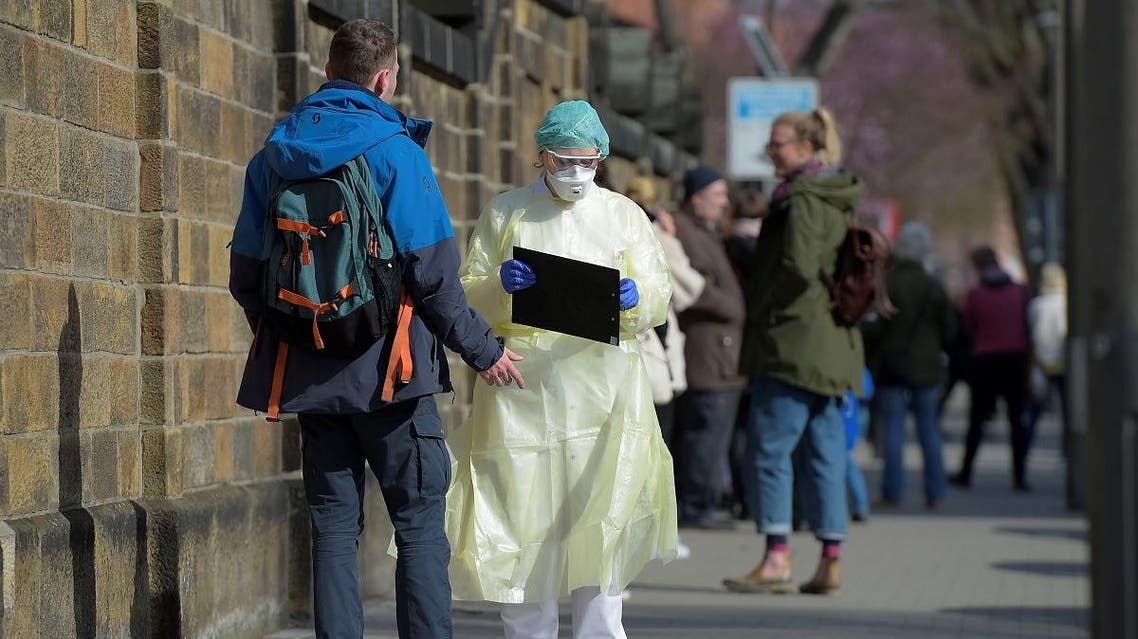 Medical staff inform people lining up for a test in a coronavirus disease (COVID-19) clearing-up centre in Dresden, Germany, March 16, 2020. (Reuters)