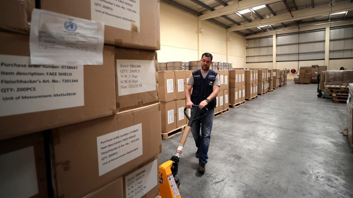 A worker pulls a cart of coronavirus aid items being prepared for shipment, at a World Health Organization, WHO, facility, part of the International Humanitarian City, in Dubai, United Arab Emirates. (AP)