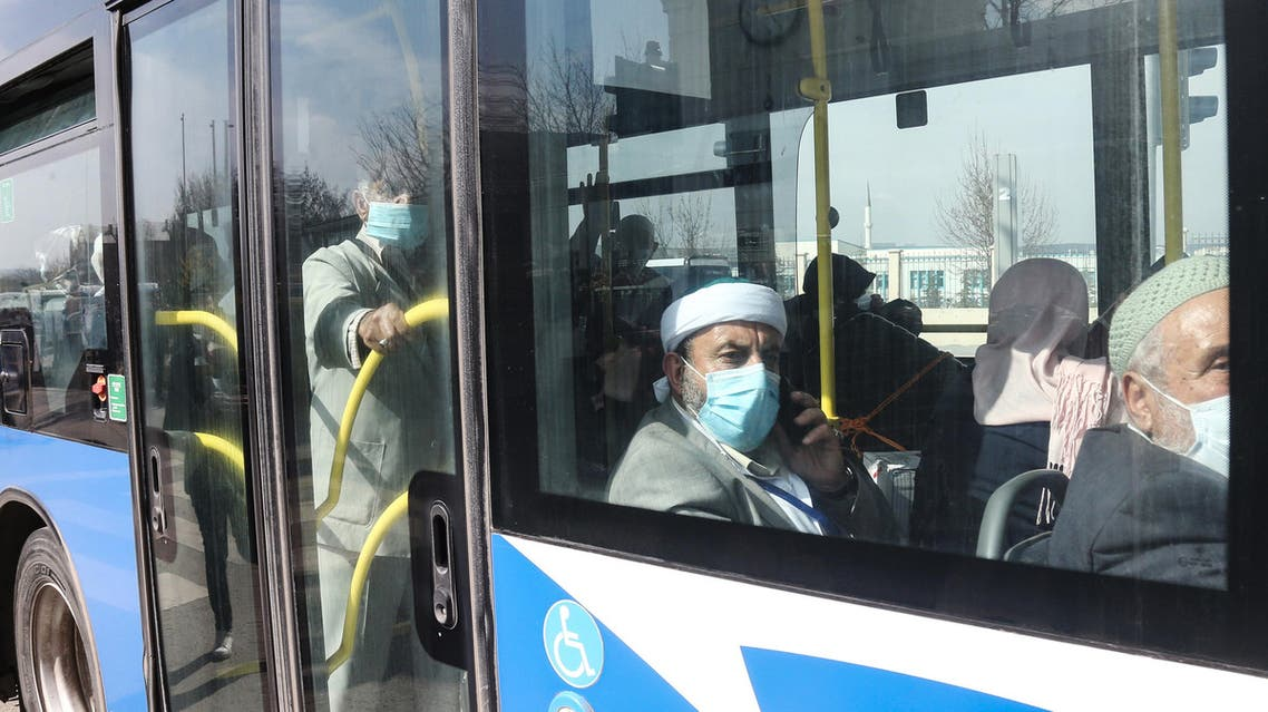 Turkish citizens wearing protective face masks sit in a bus as they are repatriated from the Umrah pilgrimage in Saudi Arabia, prior to being placed in quarantine as part of measures to limit the spread of the coronavirus, on March 15, 2020, in Ankara. (AFP)