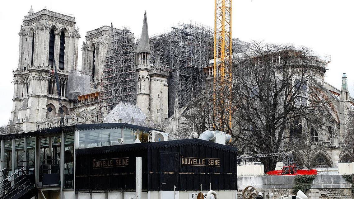 This picture taken on March 11, 2020, shows a barge parked in front of the Notre Dame Cathedral in Paris which was partially destroyed by a fire in April, 2019. (AFP)