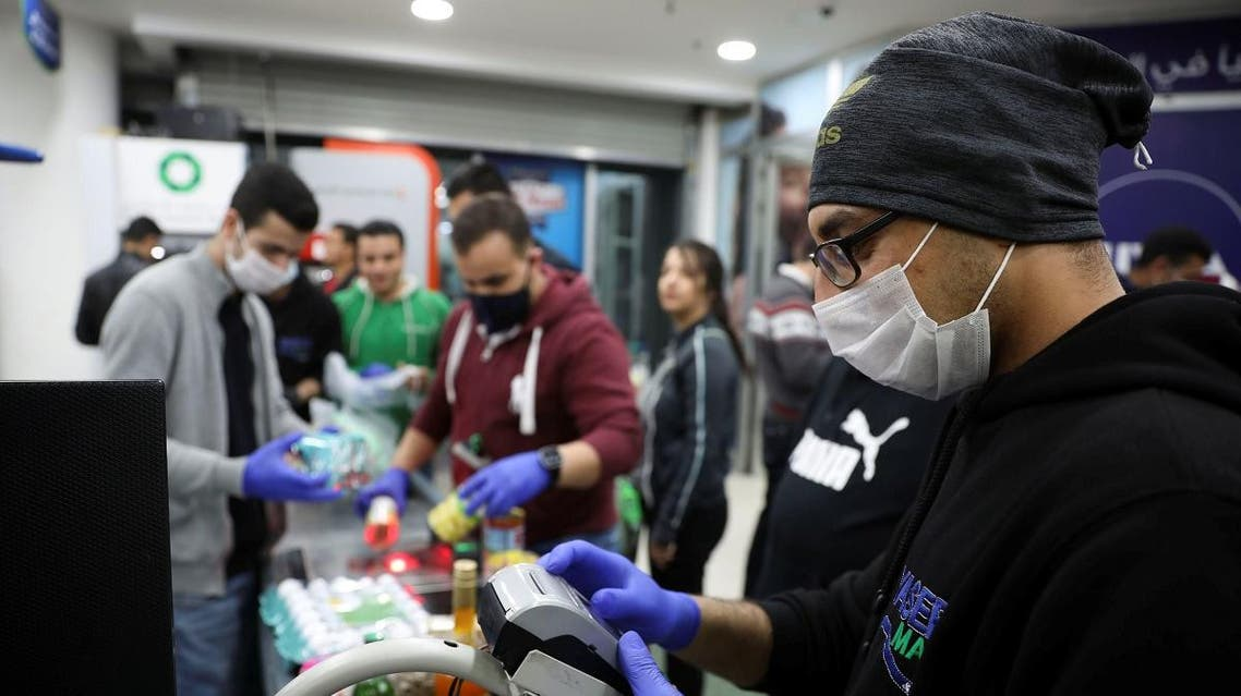 A cashier wearing a face mask amid concerns over the coronavirus spread works at a mall in Amman, Jordan, March 15, 2020. (Reuters)