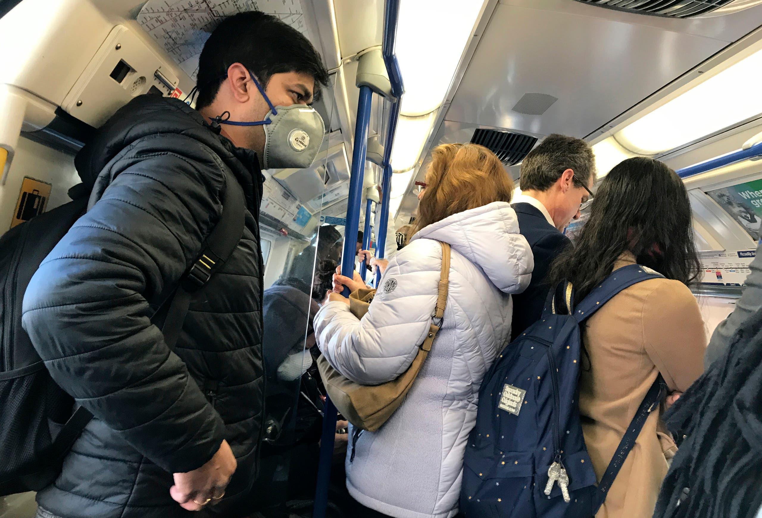 A traveler wears a mask on a busy tube in London on March 16, 2020. (AP)