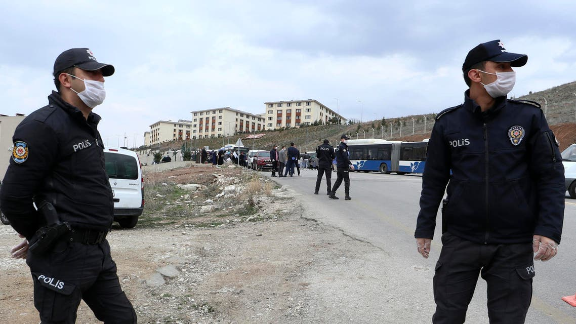 Police officers secure the area as pilgrims arrive from the airport to be quarantined in university dormitories outside Ankara on March 15, 2020. (AP)