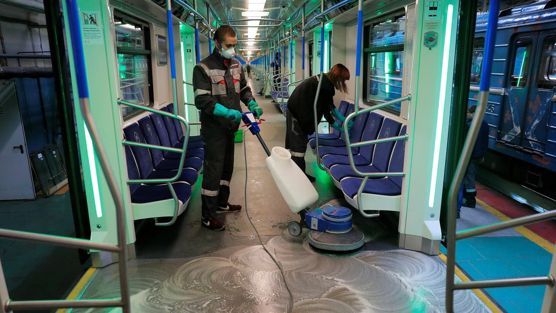 Employees wearing protective face masks clean and disinfect a subway train, as part of measures to prevent the spread of coronavirus (COVID-19) in Moscow, Russia, on March 16, 2020. (Reuters)
