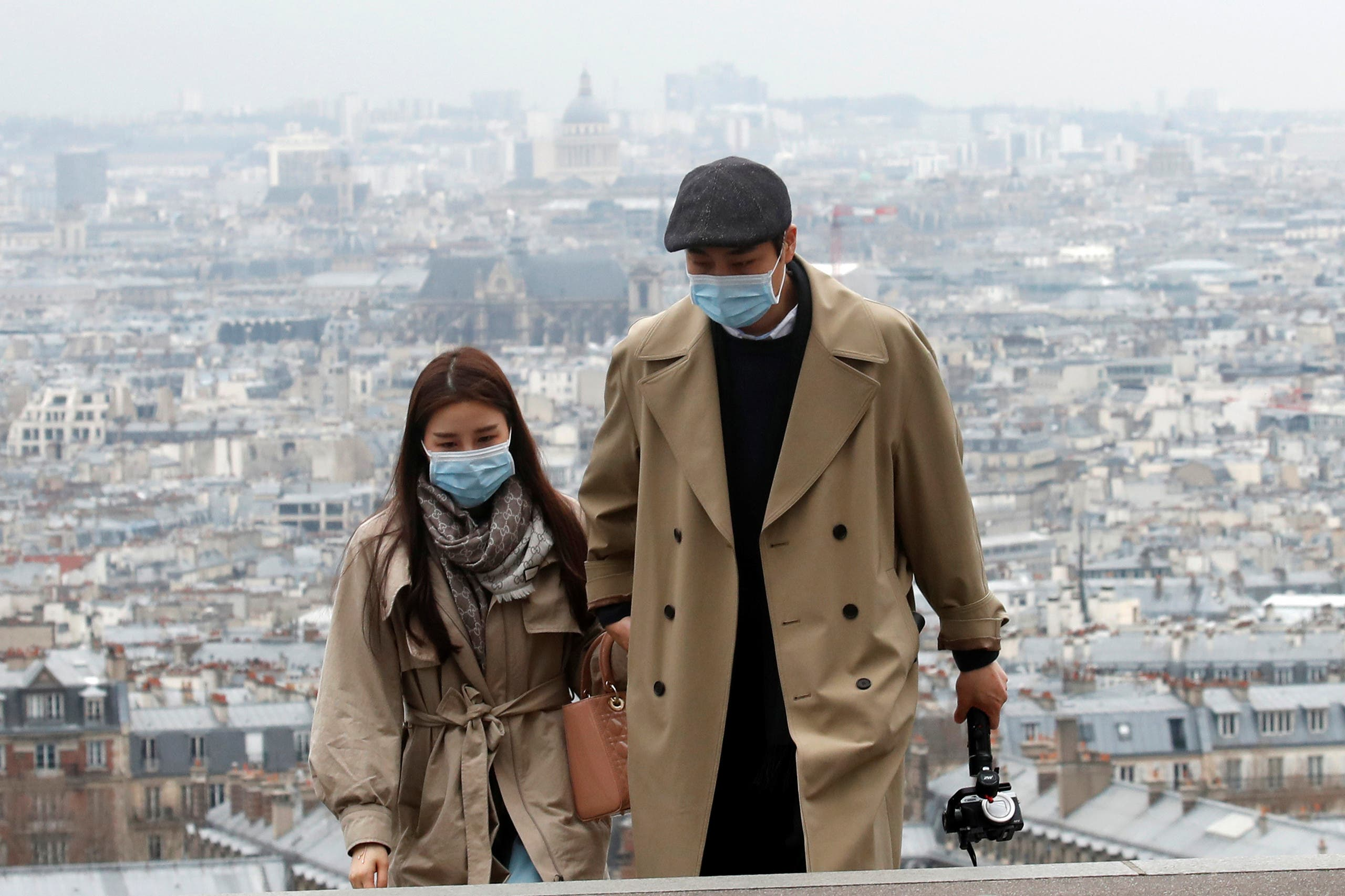 People wearing protective face masks walk in the gardens of the Montmartre's Sacre Coeur Basilica in Paris as shops, schools remain closed and workers asked to work from home if possible, part of the French government's measures against the coronavirus outbreak, France, March 16, 2020. (Reuters)
