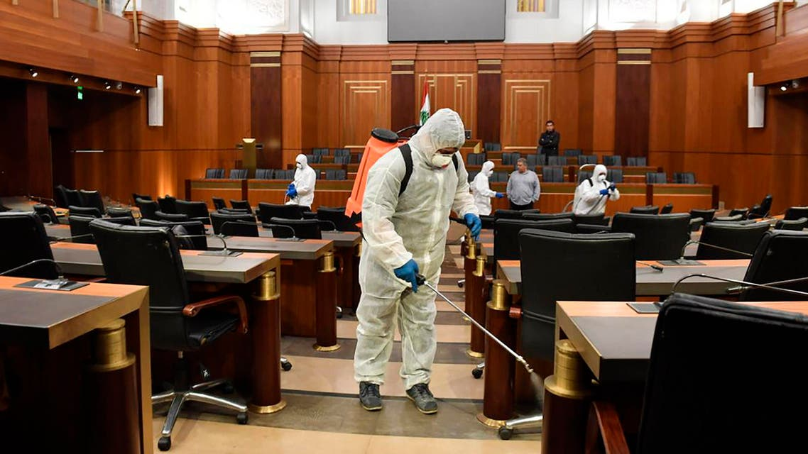 Workers wearing protective gear spray disinfectantat the main hall of the Lebanese Parliament, in Beirut on March 10, 2020. (AP)
