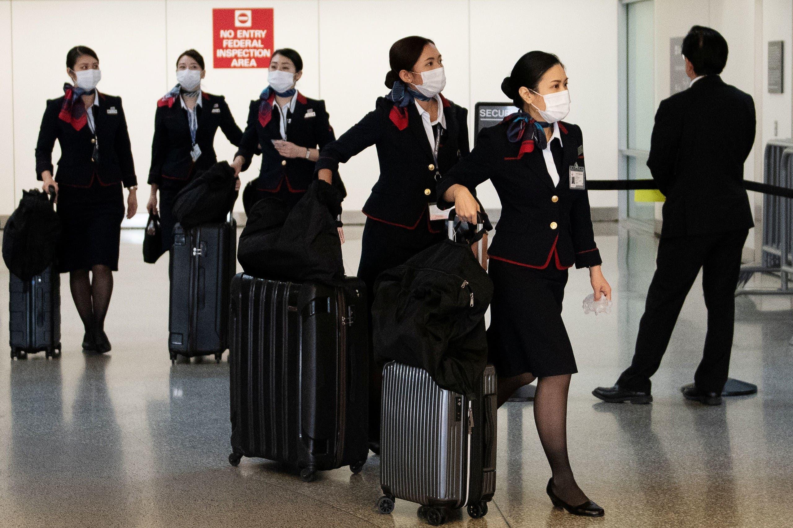 مضيفات جويات من الخطوط الجوية اليابانية يضعن أقنعة واقية في مطار سان فرانسيسكو بولاية كاليفورنيا الأميركية في صورة بتاريخ 13 مارس