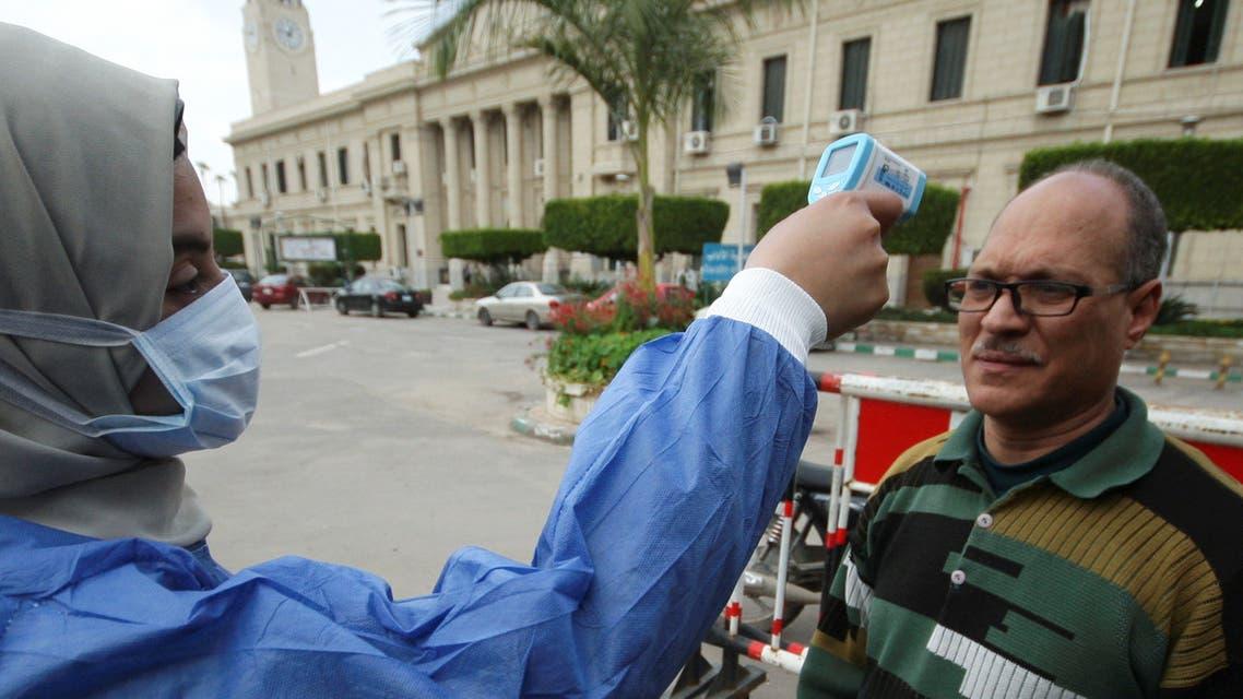 احدى العاملات بالرعاية الصحية تفحص حرارة شخص في جامعة القاهرة يوم 15 مارس