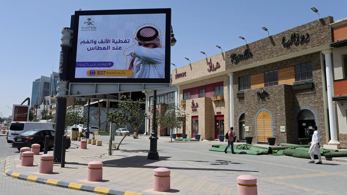 "People walk near a banner with an instruction on personnel hygiene, following the outbreak of coronavirus, at a street in Riyadh, Saudi Arabia, March 16, 2020. The banner reads: ""Wash hands with soap and water."" (Reuters)"