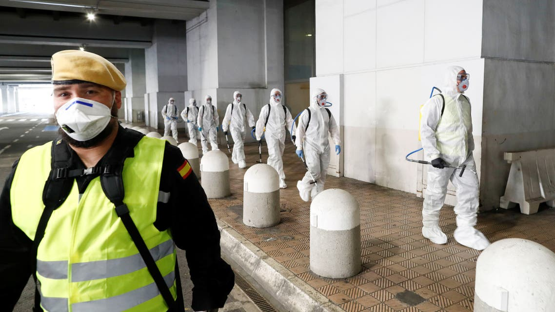 Members of the Military Emergency Unit (UME) walk to disinfect the Malaga-Costa del Sol international airport during a partial lockdown as part of a 15-day state of emergency to combat the coronavirus disease outbreak in Malaga, Spain March 16, 2020. REUTERS/Jon Nazca