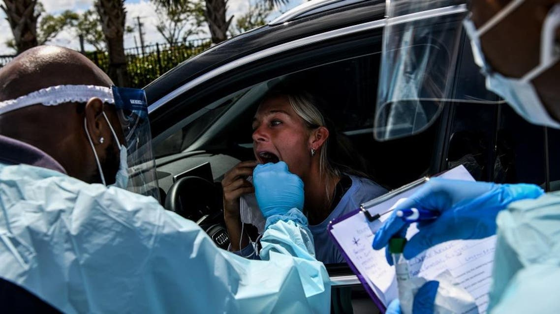 "A medical personnel member takes samples of Lee Dinzik (29) at a ""drive-thru"" coronavirus testing lab. AFP"