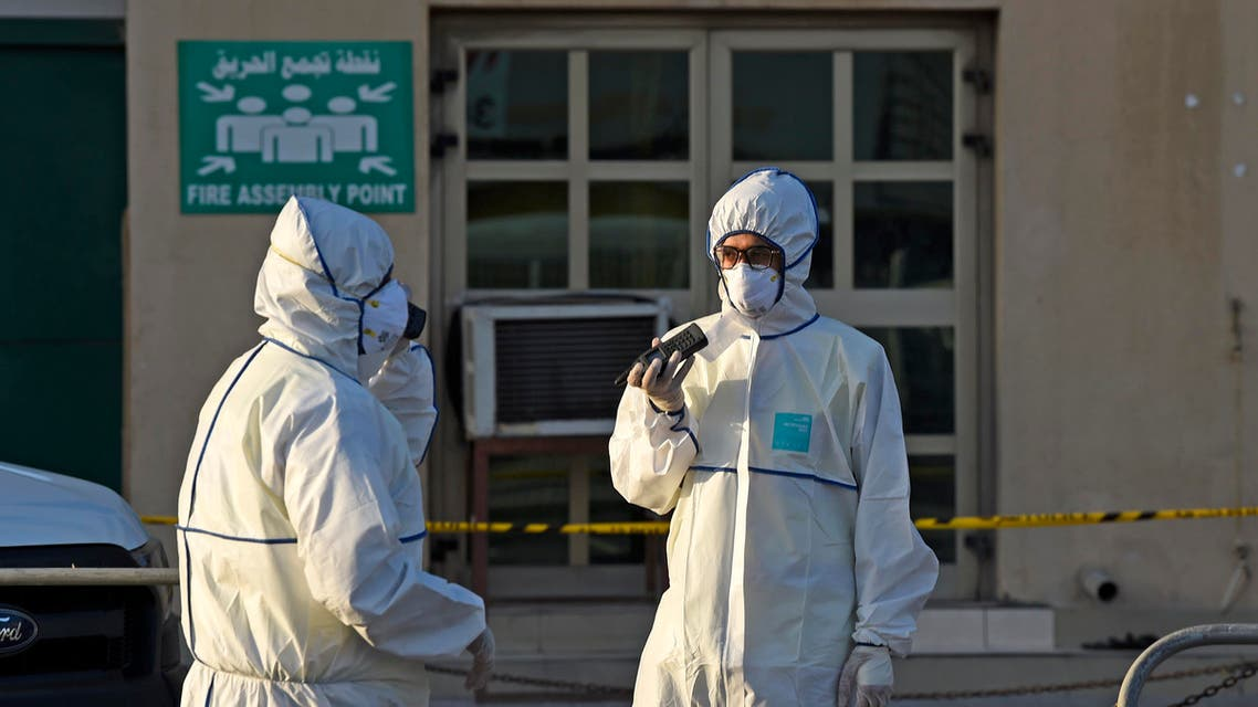 Bahraini policemen seal off a building housing foreign workers in the Salmabad industrial area as a precautionary measure after a resident tested positive for coronavirus (COVID-19), on the outskirts of the capital Manama on March 13, 2020. (AFP)