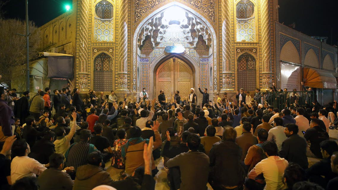 People gather outside the closed doors of the Fatima Masumeh shrine in Iran's holy city of Qom on March 16, 2020. (AFP)