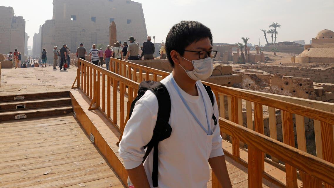 سائح يضع قناعاً واقياً بمعبد الأقصر في صعيد مصر في صورة بتاريخ التاسع من مارس