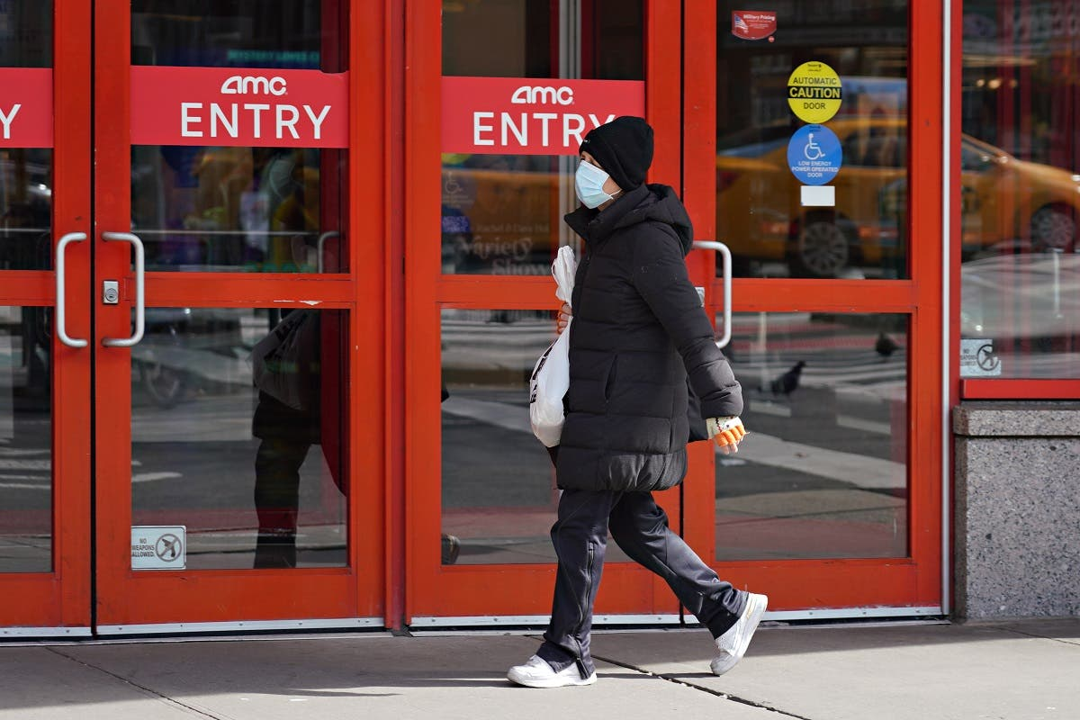 A person wears a protective mask while walking by an AMC movie theater as the coronavirus continues to spread across the United States on March 16, 2020 in New York City. (AFP)