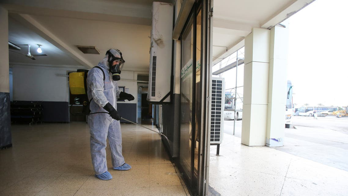 A worker wearing a protective suit disinfects a bus station, following the outbreak of coronavirus disease (COVID-19), in Algiers, Algeria March 16, 2020. REUTERS/Ramzi Boudina