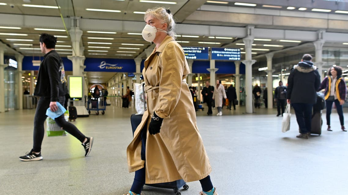 A woman wearing a protective face mask passes through the Eurostar terminal at St Pancras International station in central London on March 17, 2020. The rail and maritime companies providing transport between France and Great Britain were adapting on Tuesday, March 17, to the new containment measures in France and to the closure to non-Europeans of the Schengen area. Eurostar, which runs high-speed trains between London and the mainland, canceled half of its trains on Tuesday.