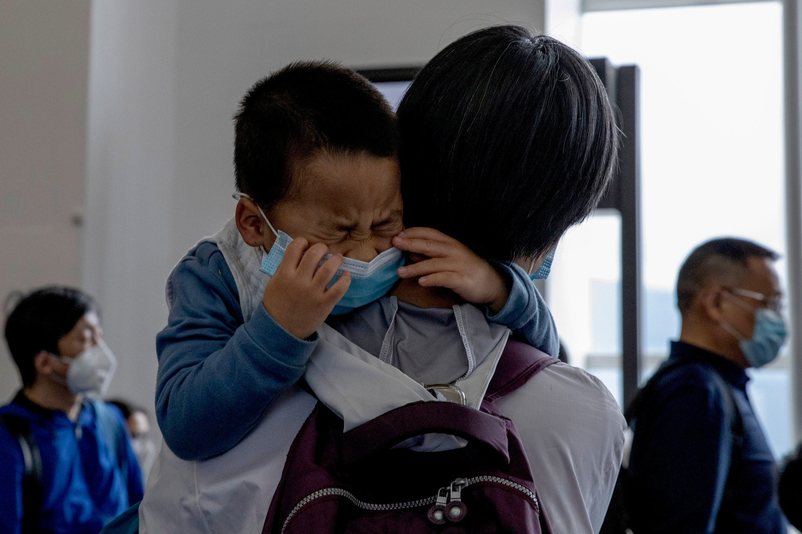A child cries as he waits in line to board a plane for Beijing at the airport in Hong Kong on Feb. 9, 2020. (AP)