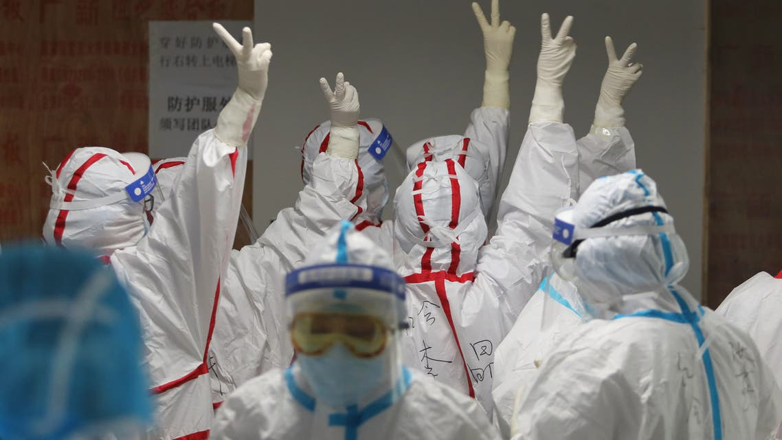 Medical staff cheer themselves up before going into an ICU ward for COVID-19 coronavirus patients at the Red Cross Hospital in Wuhan in China's central Hubei province on March 16, 2020. China reported 12 more imported cases of the novel coronavirus on March 16 as the capital tightened quarantine measures for international arrivals to prevent a new wave of infections.