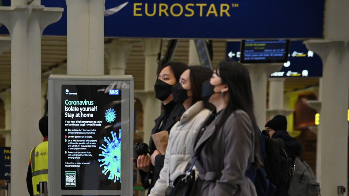 A notice warning people of the Coronavirus, is displayed as passengers wearing protective face masks pass through the Eurostar terminal at St Pancras International station in central London on March 17, 2020. The rail and maritime companies providing transport between France and Great Britain were adapting on Tuesday, March 17, to the new containment measures in France and to the closure to non-Europeans of the Schengen area. Eurostar, which runs high-speed trains between London and the mainland, canceled half of its trains on Tuesday.