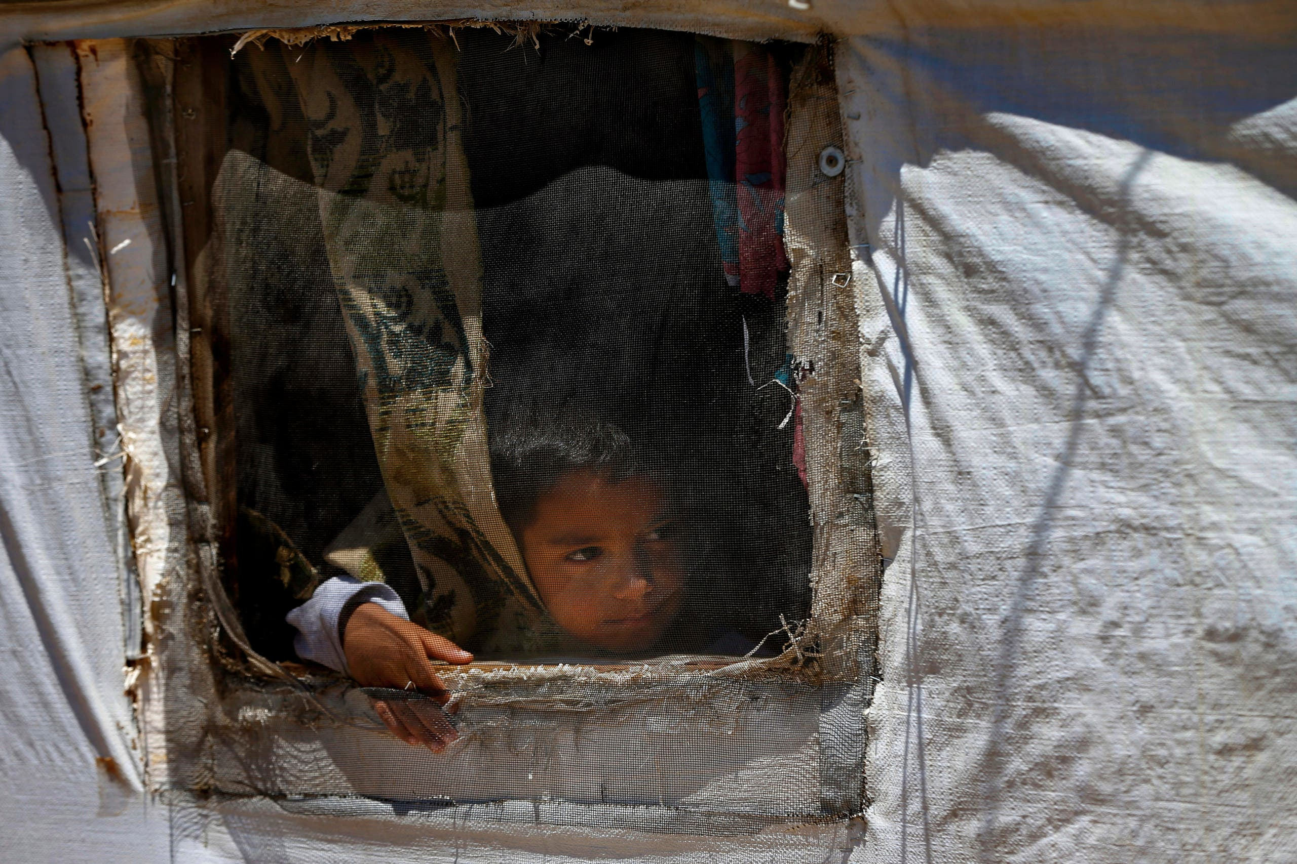 A Syrian refugee child looks through a window in his family tent in a refugee camp in the border town of Arsal, Lebanon, on June 16, 2019. (AP)