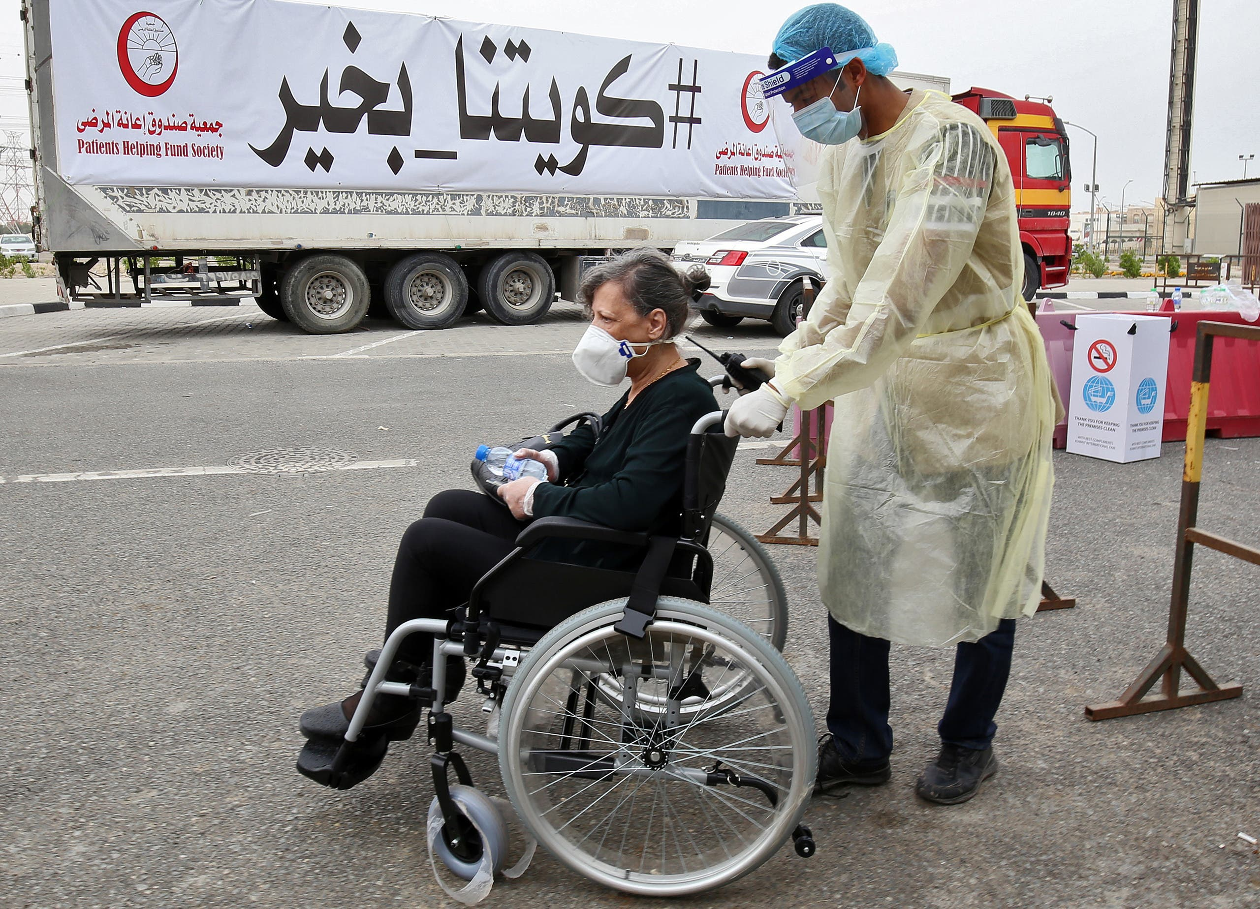 A woman is pushed on a wheelchair as she arrives at a Kuwaiti health ministry containment and screening zone for coronavirus disease for expatriates returning from Egypt, Syria, and Lebanon, in Kuwait City on March 15, 2020. (AFP)