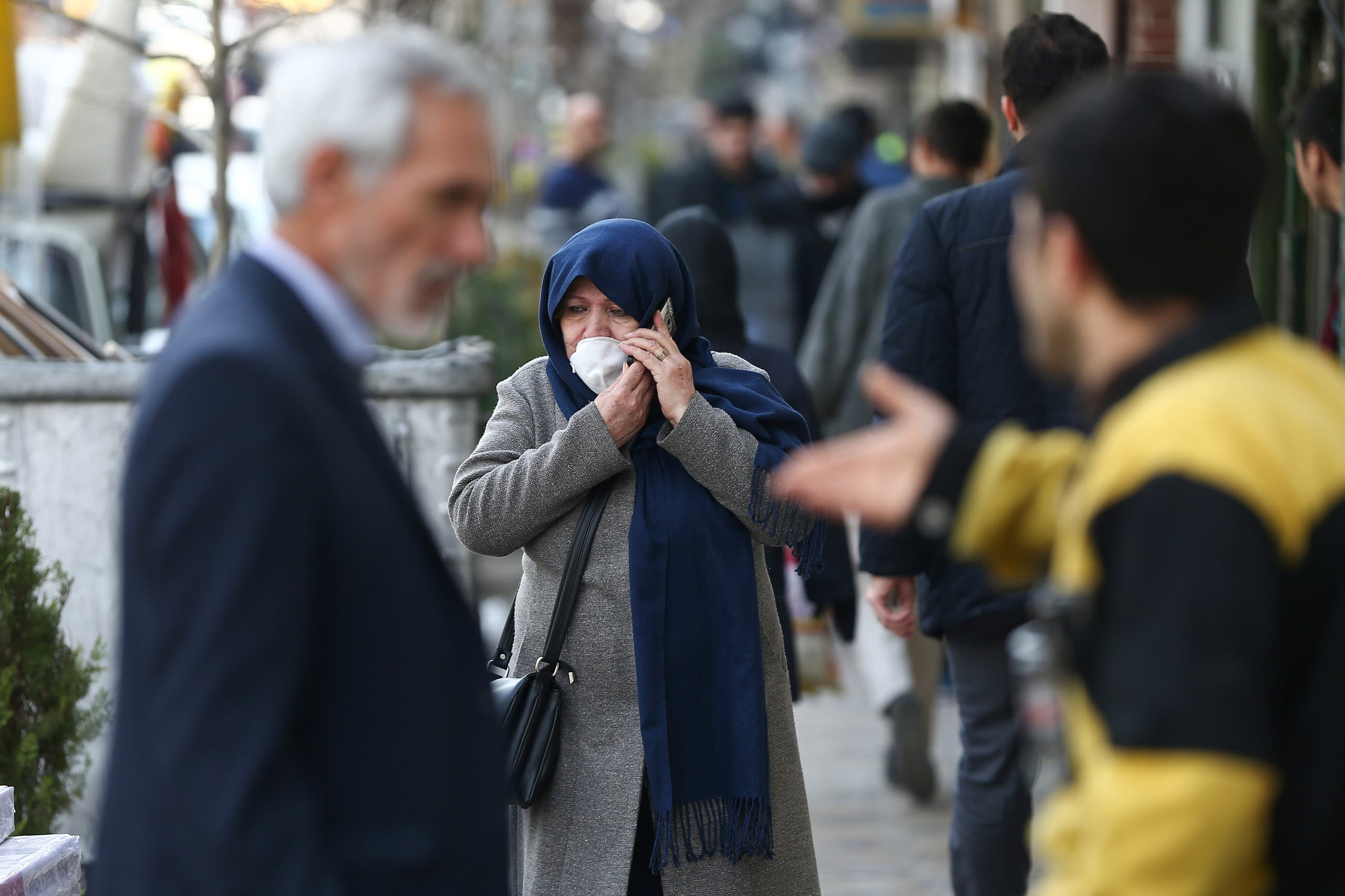 An Iranian woman wears a protective face mask, following the coronavirus outbreak, as she talks on the phone, in Tehran, Iran March 5, 2020. (Reuters)