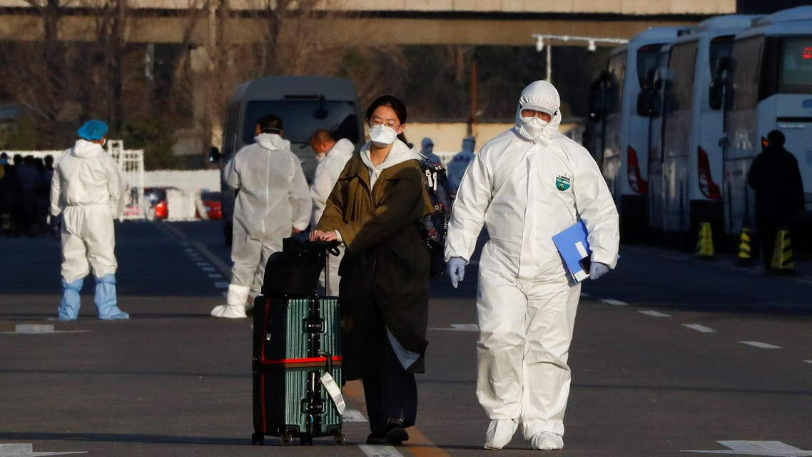 Staff in protective suits accompany passengers outside a centralized facility for screening and registration near the Beijing Capital International Airport in Beijing as the country is hit by an outbreak of the novel coronavirus, China, March 17, 2020. REUTERS