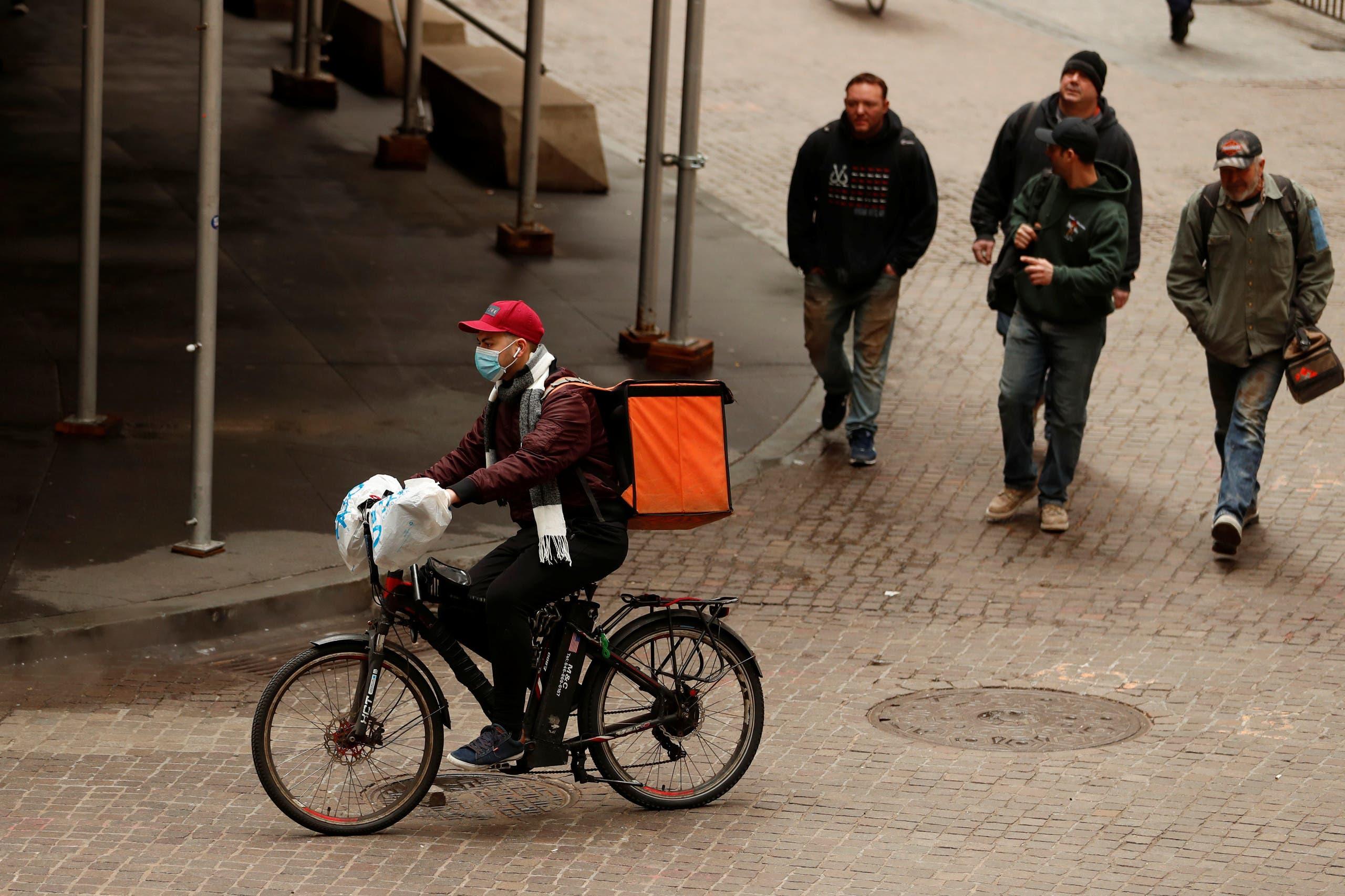 عامل توصيل طلبات يضع قناعاً واقياً في نيويورك الثلاثاء