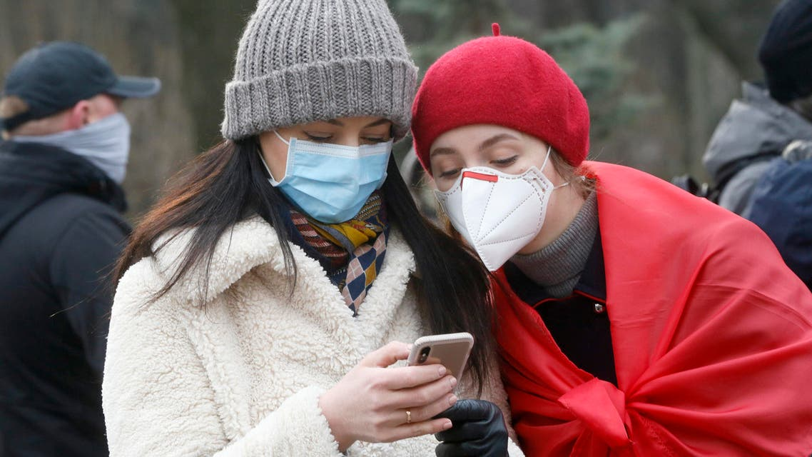 Ukrainians wearing face masks look at the latest news on a phone in Kyiv, Ukraine, Tuesday, March 17, 2020. (AP)