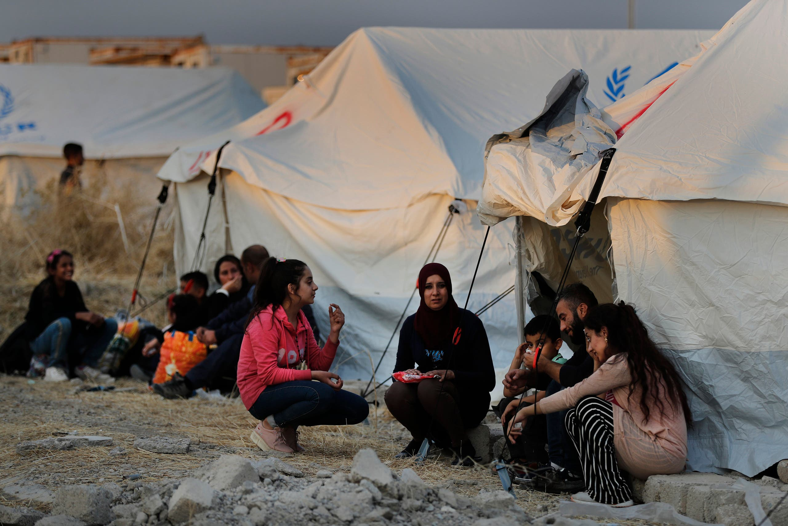 Syrians wait to receive tents and aid supplies at the Bardarash refugee camp, north of Mosul, Iraq on Oct. 17, 2019. (AP)