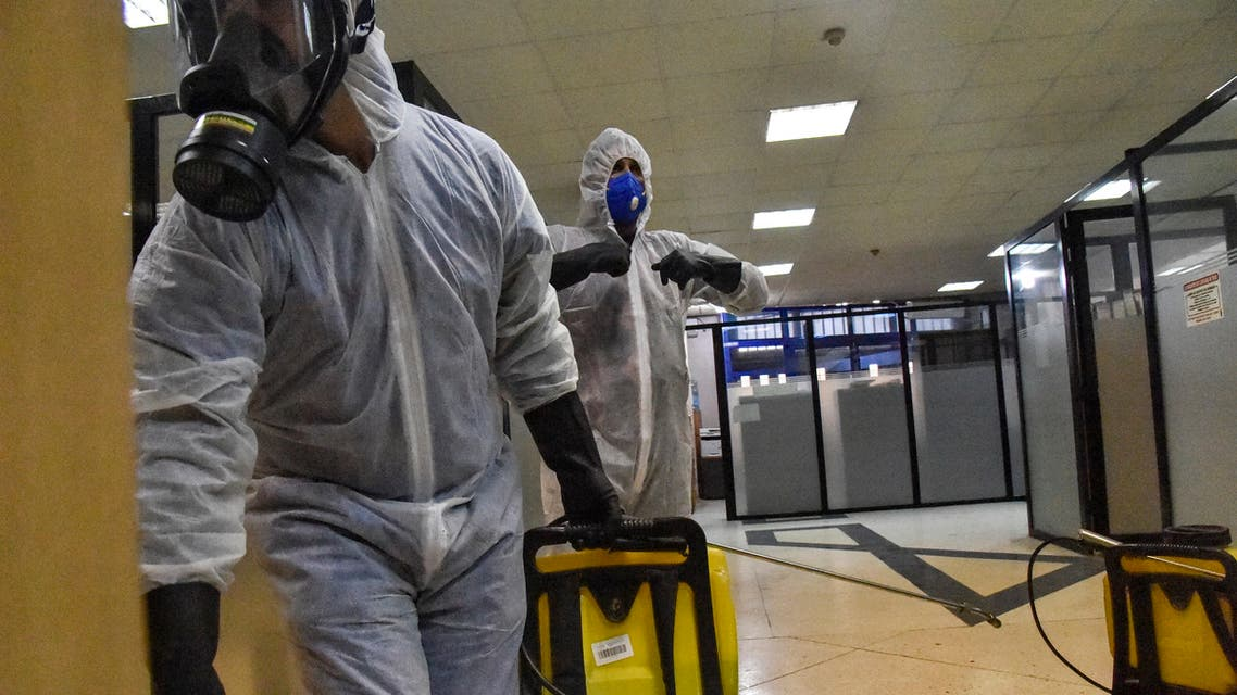 Algerian municipal workers disinfect the Kherrouba bus station against the coronavirus COVID-19, in Algiers on March 16, 2020.