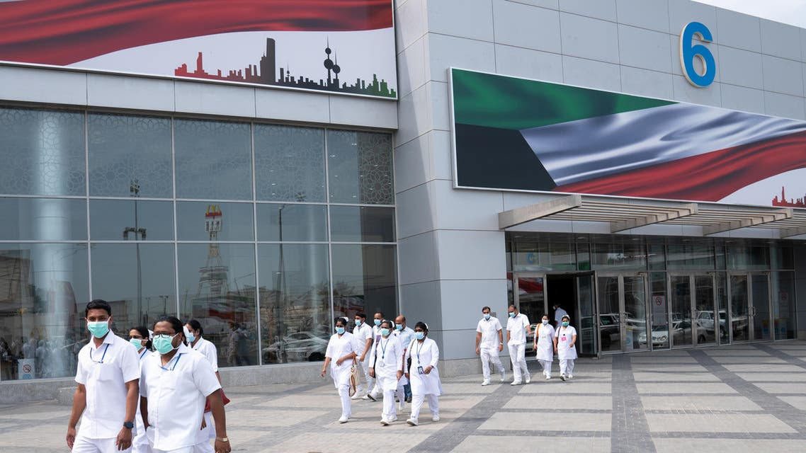 Nurses walk in front of a makeshift coronavirus testing center at the Mishref Fair Grounds in Kuwait city. (Reuters)
