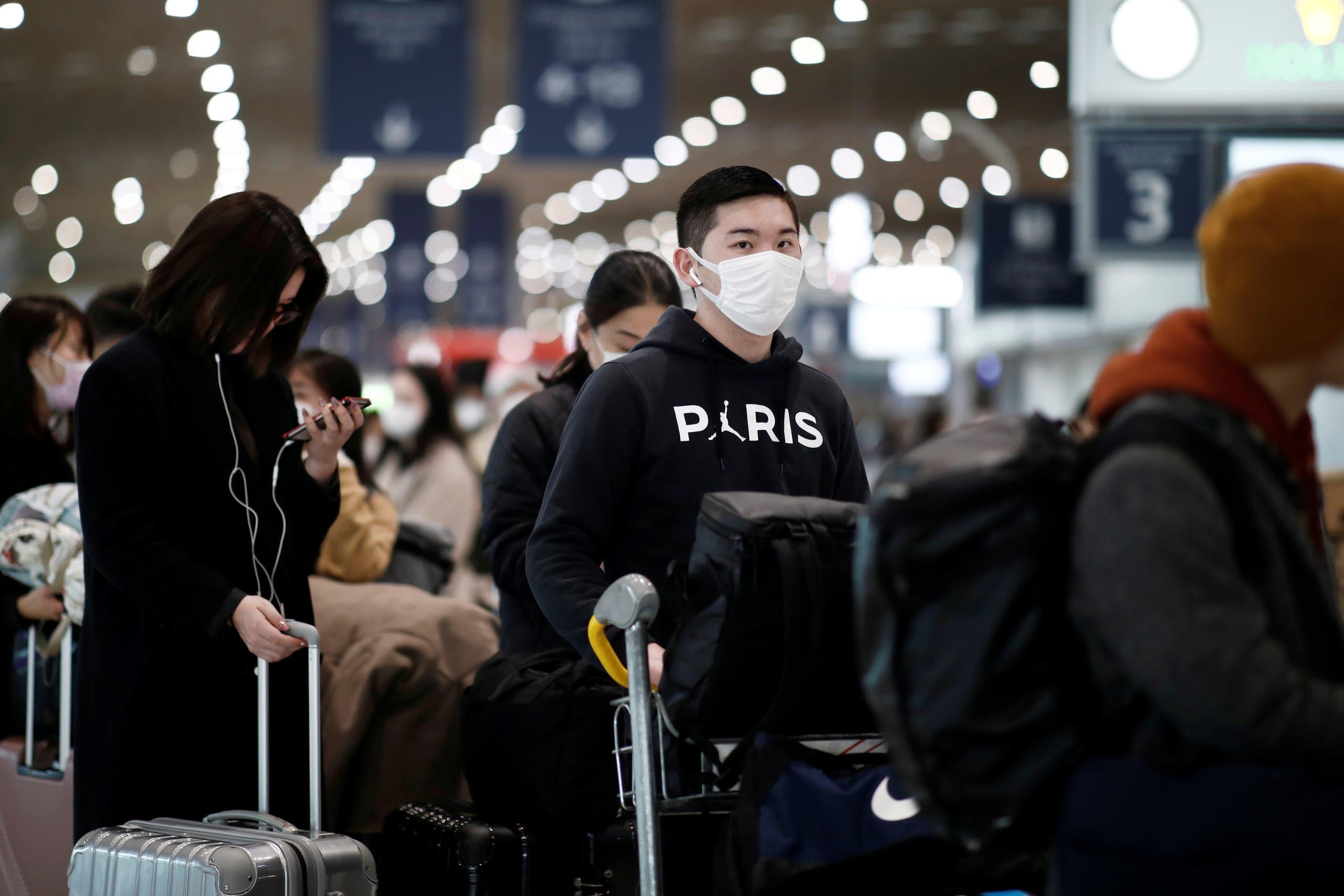 رجل يضع قناعاً واقياً في مطار شارل ديغول الاثنين