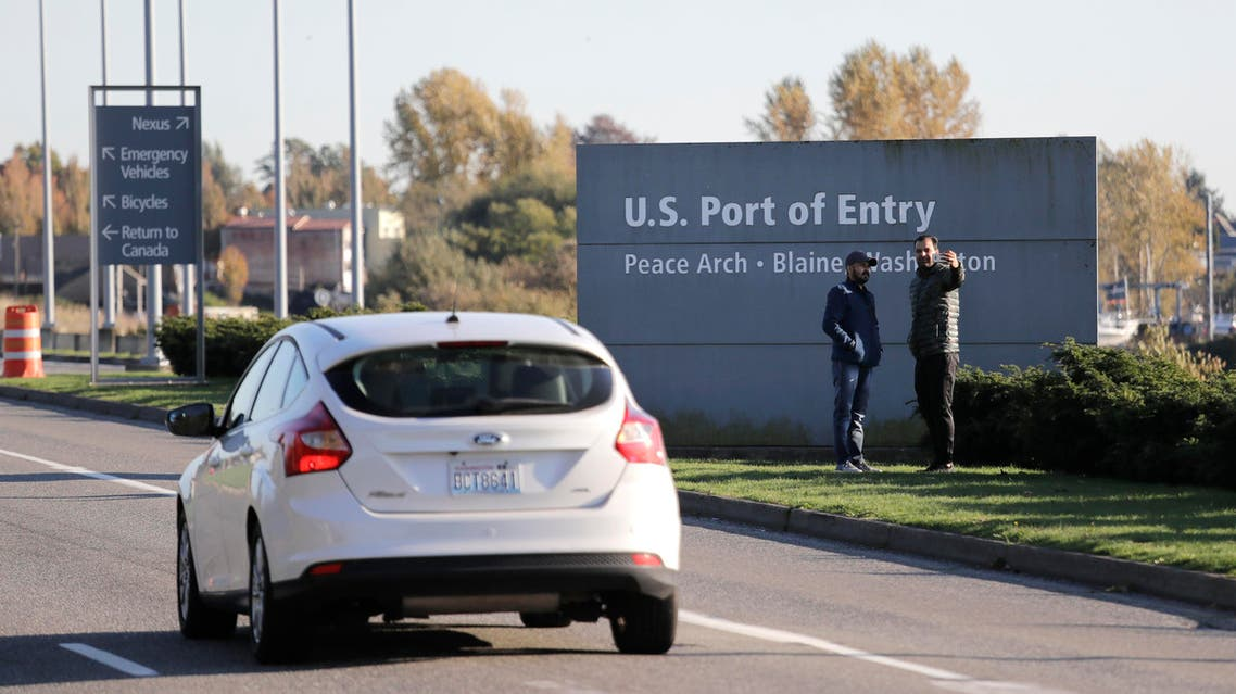 two pedestrians take a photo at an entry sign as traffic enters the United States from Canada at the Peace Arch Border Crossing, in Blaine, Wash. (AP)