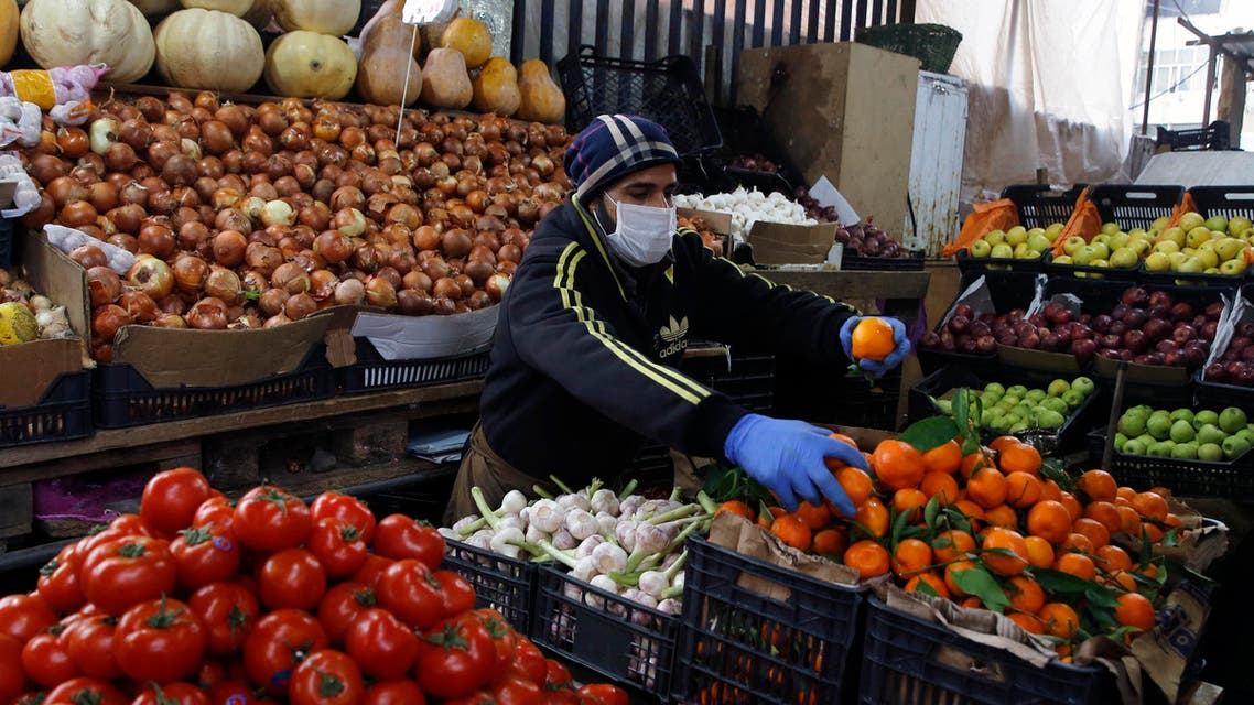 Syrian Sami Jawabreh wears a mask and gloves, as he rearranges fruits on display for sale at his shop, in Beirut on March 18, 2020. (AP)