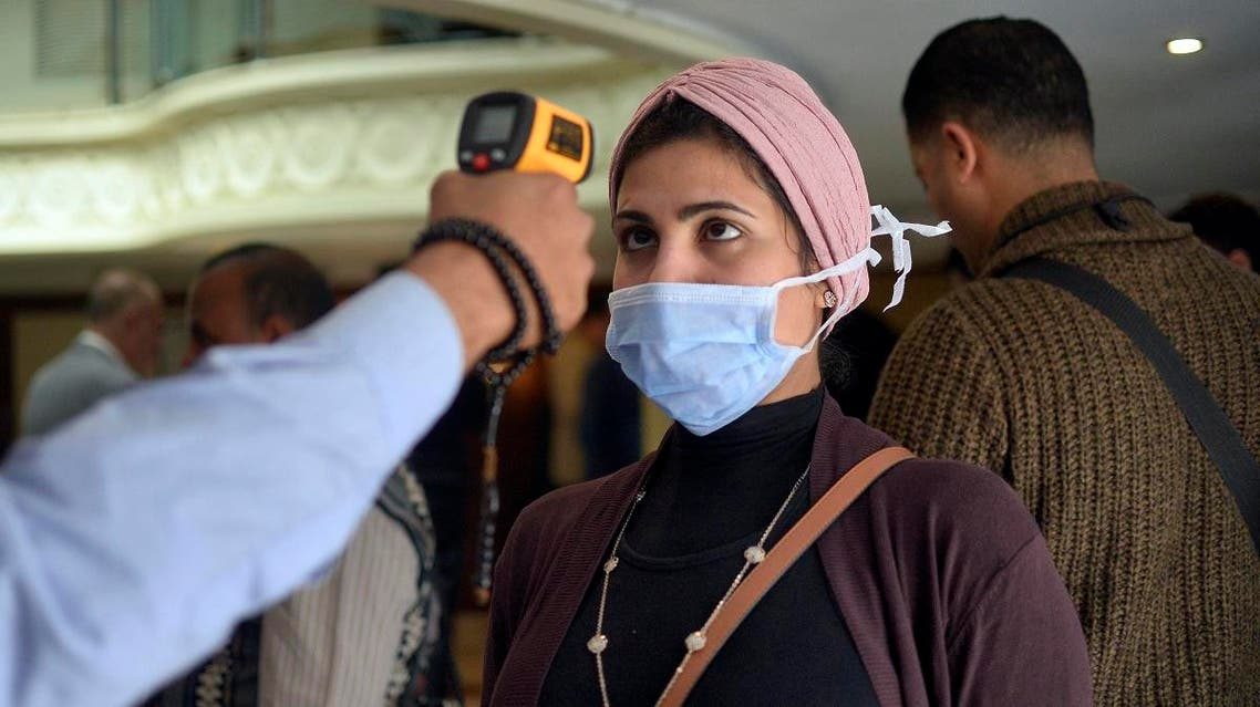 A woman wearing a protective health mask has her body temperature measured at on a touristic river boat in Egypt's southern city of Luxor on March 8, 2020. (AFP)