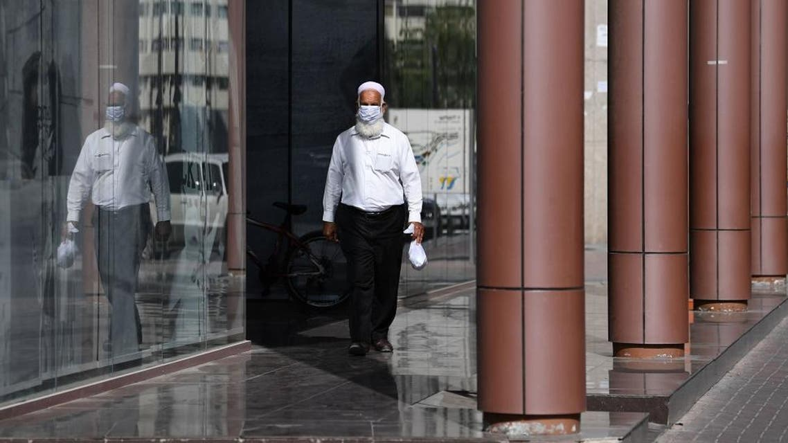 A man wearing a protective mask walks down the street in Dubai on March 18, 2020 amidst the coronavirus COVID-19 pandemic. (AFP)