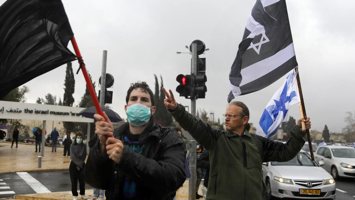 A man waves an Israeli flag and another Israeli flag with the colors inverted standing next to another mask-clad man waving a plain black banner, during a protest outside the Knesset (parliament) in Jerusalem on March 19, 2020. (AFP)