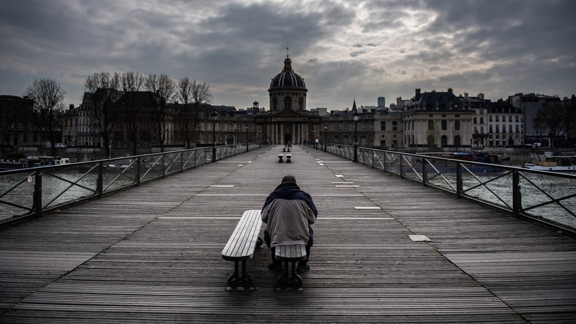 A man waits on a bench of the Pont Des Arts in Paris, France, on March 17, 2020 as a strict lockdown comes into in effect to stop the spreading of the COVID-19 in the country. (AFP)