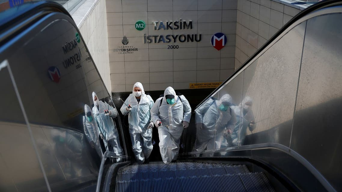 Municipality workers in protective suits disinfect entrance of Taksim metro station in central Istanbul, Turkey, March 17, 2020. (Reuters)